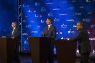 Virginia Democratic gubernatorial candidate and former Gov. Terry McAuliffe, left, debates Republican challenger, Glenn Youngkin, while moderator Chuck Todd, right, looks on, at Northern Virginia Community College, in Alexandria, Va., Tuesday, Sept. 28, 2021. (AP Photo/Cliff Owen)