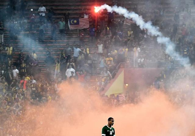 Yasyn Alnakhli of Saudi Arabia walks off the pitch after flares were thrown on the pitch during the 2018 World Cup qualifying football match between Malaysia and Saudi Arabia in Shah Alam on September 8, 2015 (AFP Photo/Manan Vatsyayana)
