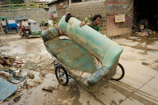 A man uses a bicycle to transport a sofa chair in Tomana slum, Marikina city in the suburbs of Manila on August 11. Deadly floods, power blackouts and traffic gridlock -- many of Asia's biggest cities are buckling under the strain of rapid economic development, extreme weather and an exodus from the countryside