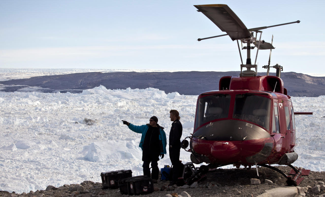 In this July 19, 2011 photo, with the Jakobshavn ice fjord visible in the background, NYU researcher David Holland, left, discusses logistics with a helicopter pilot before flying to deploy devices designed to track glacial movement near the edge of the Greenland Ice Sheet, outside Ilulissat, Greenland. Holland hopes to eventually deploy scores of the devices to help measure ice loss in Greenland. (AP Photo/Brennan Linsley)