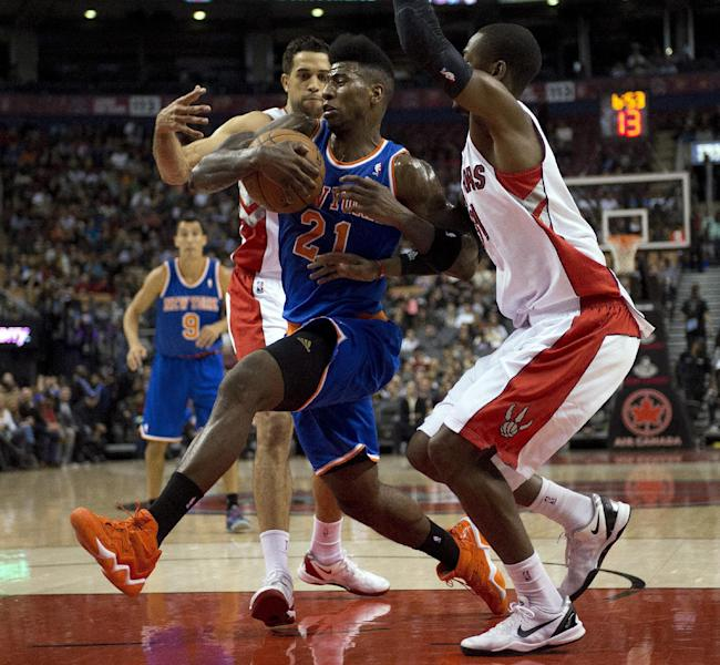 New York Knicks' Iman Shumpert (21) drives to the hoop between Toronto Raptors' Landry Fields, left, and Terrence Ross, right, during first-half NBA basketball preseason game action in Toronto, Friday, Oct. 11, 2013. (AP Photo/The Canadian Press, Frank Gunn)