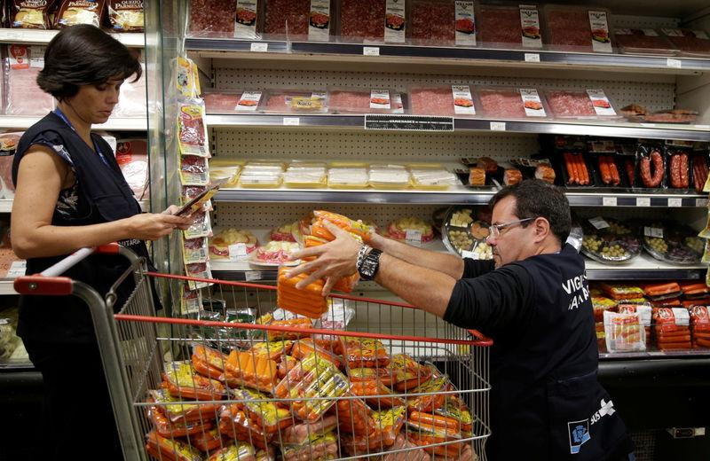 Members of the Public Health Surveillance Agency collect sausages to analyse in their laboratory, at a supermarket in Rio de Janeiro