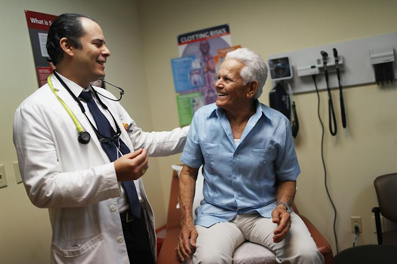 Ivan Mendoza, MD, associate medical director for the Jackson Medical Group's cardiology practice, (L) speaks with Felipe Finale, 78, during a media event at Jackson South Community Hospital to announce his successful implant of the world's smallest pacemaker.