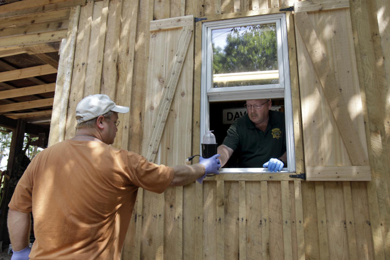 FILE - In this Sept. 2, 2010 file photo, Franklin County Detective Don Blankenship, right, hands evidence through a window to fellow detective Darryl Balleydier during a raid of a suspected meth house in Gerald, Mo. Several states ravaged by methamphetamine may have to scale back efforts to bust the labs that produce the drug because federal funds dedicated to helping states clean up the toxic sites have dried up, officials say. (AP Photo/Jeff Roberson, File)