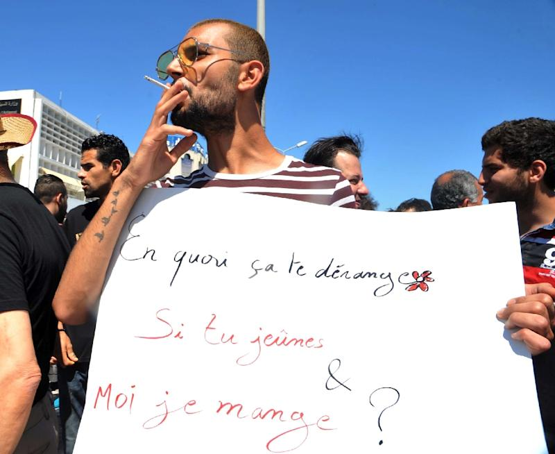 "A protester in Tunis openly smokes a cigarette and holds a placard reading in French ""Why does it bother you if you fast and I eat?"" during Ramadan on June 11, 2017"