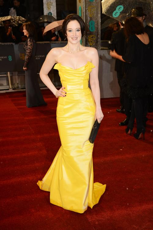 Andrea Riseborough went for an eye-popping yellow Vivienne Westwood gown, later sharing pal Anne Hathaway's coat to keep warm. <br><br>©Getty