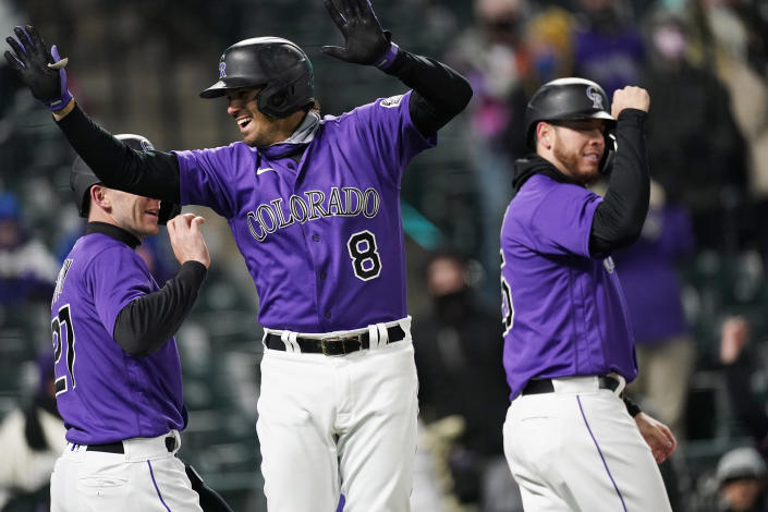Colorado Rockies' Josh Fuentes, center, celebrates his three-run home run with Trevor Story, left, and C.J. Cron off New York Mets relief pitcher Jacob Barnes during the fifth inning of the second game of a baseball doubleheader Saturday, April 17, 2021, in Denver. (AP Photo/David Zalubowski)
