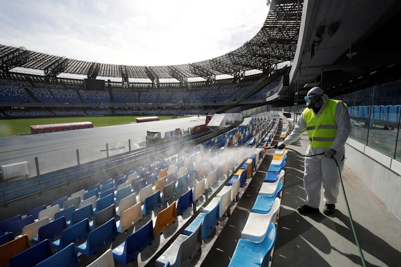 A cleaner wearing a protective suit sanitises seats at the San Paolo stadium ahead of the second leg of the Coppa Italia semi-final between Napoli and Inter Milan, which has since been postponed as part of measures to contain the coronavirus outbreak, in Naples, Italy, March 4, 2020. REUTERS/Ciro De Luca