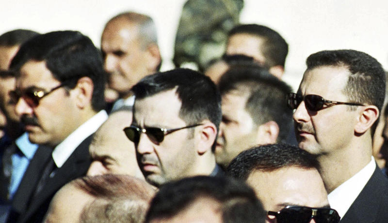 FILE - In this picture taken on June 13, 2000, Syrian President Bashar al-Assad, right, his brother Maher, centre,  and brother-in-law Major General Assef Shawkat, left, stand during the funeral of late president Hafez al-Assad in Damascus, Syria. Syria's President Bashar Assad, beset by a popular upheaval that won't die, appears to be turning more and more to a tiny coterie of relatives, the backbone of a family dynasty that has kept Syria's 22 million people living in fear for decades. (AP Photo, File)