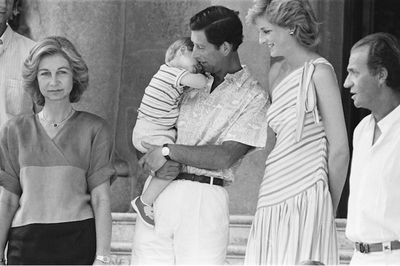 Princess Diana,The Princess of Wales and her husband Prince Charles, The Prince of Wales on holiday in Palma, Majorca. They are the guests of King Juan Carlos (right) and his wife Sofia (left) , and are pictured here at Marivent Palace, Palma, Majorca. In this picture Prince Charles holds a sleepy nearly 2 year old Prince Harry, 9th August 1986. (Photo by Geoff Garratt/Sunday Mirror/Mirrorpix/Getty Images)