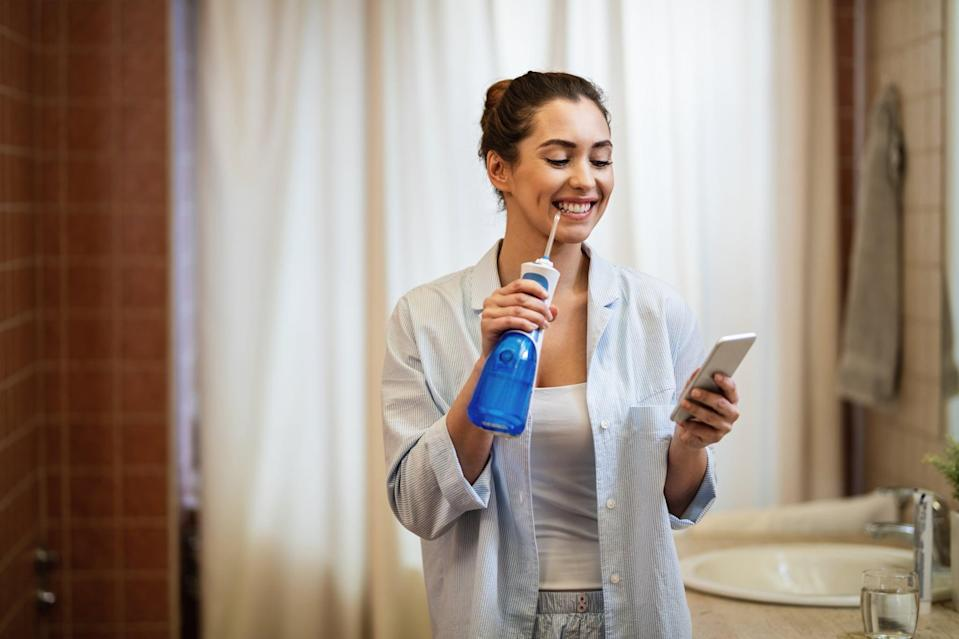Young happy woman using dental water flosser and cleaning her teeth while texting on mobile phone in the bathroom.