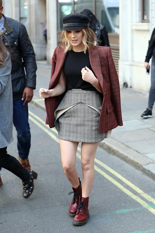 <p><strong>How to get the look</strong>: Mix two different shades of plaid in the form of a blazer and a skirt. Neutralize the mismatch with a black t-shirt and black newsboy cap, adding edge with cranberry combat boots.</p>