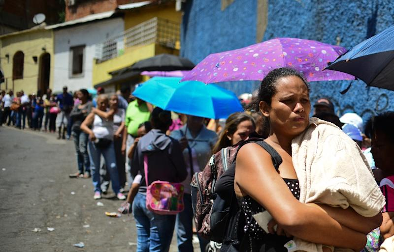 People line up to buy food and household items outside a supermarket in Caracas, Venezuela on May 27, 2016