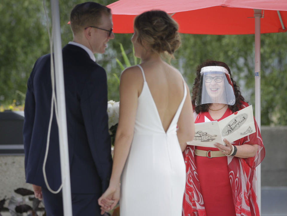 "An officiant wearing a face shield hosts an outdoor ""micro-wedding"" for a couple in Vancouver, Canada, on June 19, 2020. The pilot project was first announced in early May as an alternative for those who may have had to change their wedding plans due to the COVID-19 pandemic. (Photo by Liang Sen/Xinhua via Getty)"
