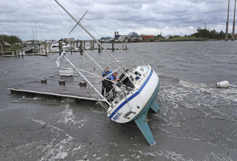 Beaufort Police Officer Curtis Resor, left, and Sgt. Micheal Stepehens check a sailboat for occupants in Beaufort, N.C. after Hurricane Dorian passed the North Carolina coast on Friday, Sept. 6, 2019. Dorian howled over North Carolina's Outer Banks on Friday — a much weaker but still dangerous version of the storm that wreaked havoc in the Bahamas — flooding homes in the low-lying ribbon of islands and throwing a scare into year-round residents who tried to tough it out.