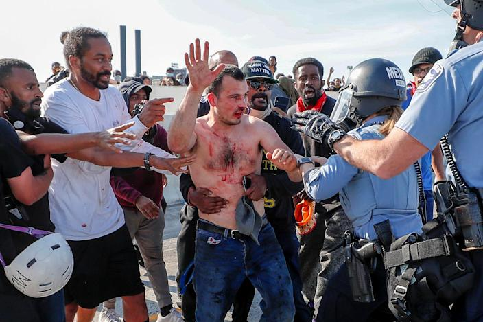Protesters hand over to the police the driver of a tanker truck after he drove into hundreds of protesters marching on 35W north bound highway during a protest against the death in Minneapolis police custody of George Floyd, in Minneapolis on May 31, 2020 (Eric Miller / Reuters file)