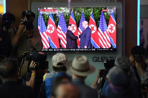 Commuters in Seoul gather around a screen at a railway station to watch live footage of the historic handshake