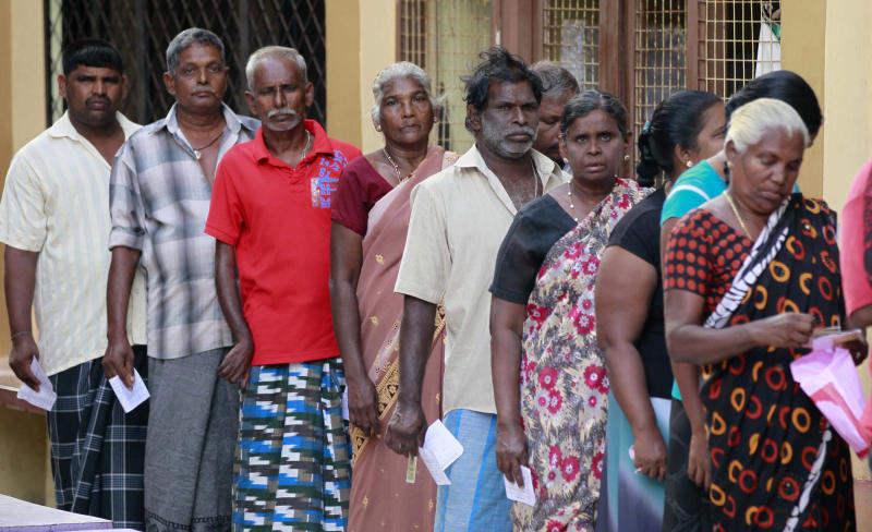 Sri Lankan ethnic Tamils wait to cast their votes at a polling station during the northern provincial council election in Jaffna, Sri Lanka, Saturday, Sept. 21, 2013. The Tamils who are concentrated in the country's northern province are taking part in the election to form their first functioning provincial council, hoping that it will be first step toward winning wider self-government which they failed to achieve over the past 60 years, first through non-violent protests and strikes and later through a bloody quarter-century civil war.(AP Photo/Eranga Jayawardena)