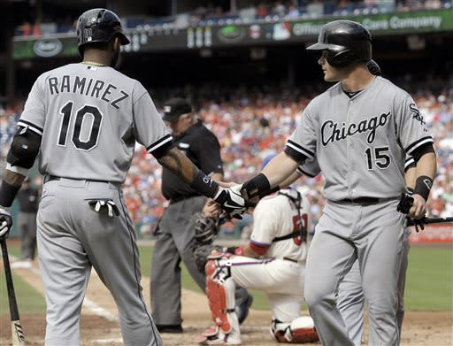 Chicago White Sox's Gordon Beckham (15) is greeted by Alexei Ramirez after scoring on an Alejandro De Aza double in the fifth inning during game one of a baseball doubleheader against the Philadelphia Phillies on Saturday, July 13, 2013, in Philadelphia. (AP Photo/Michael Perez)