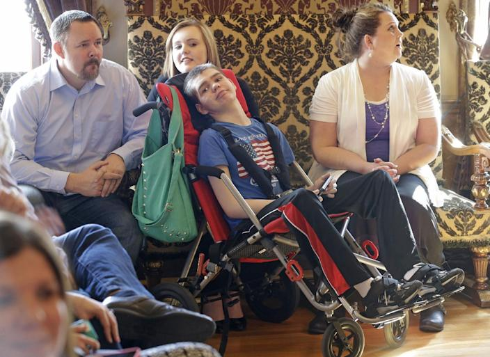 Stockton May, center, 12, waits with his sister Makayla, rear, and his mother Jennifer, right, before the H.B 105 bill signing ceremony at the Utah State Capitol, Tuesday, March 25, 2014, in Salt Lake City. Parents of Utah children with severe epilepsy are cheering a new state law that allows them to obtain a marijuana extract they say helps with seizures, but procuring it involves navigating a thorny set of state and federal laws. Utah's Republican Gov. Gary Herbert has already approved the law and held the signing ceremony Tuesday afternoon. The new law doesn't allow medical marijuana production in Utah but allows families meeting certain restrictions to obtain the extract from other states. (AP Photo/Rick Bowmer)