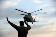 A helicopter carryying Cambodia's Prime Minister Hun Sen arrives at the port as MS Westerdam, a cruise ship that spent two weeks at sea after being turned away by five countries over fears that someone aboard might have the coronavirus, docks in Sihanoukvi