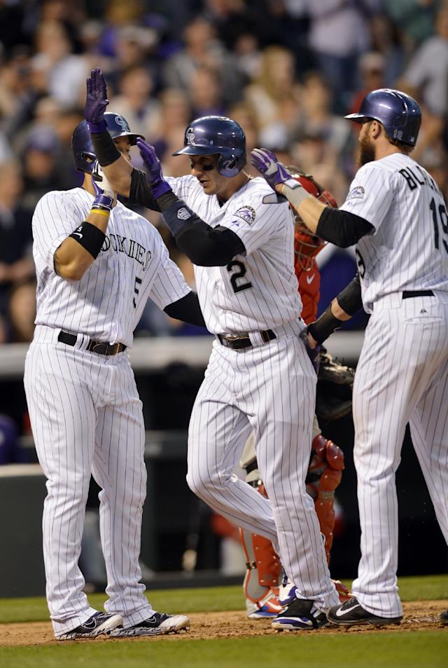 Colorado Rockies' Troy Tulowitzki (2) is congratulated by teammates Carlos Gonzalez (5) and Charlie Blackmon (19) after driving them in on a three-run home run hit off Philadelphia Phillies starting pitcher Jonathan Pettibone (44) during the second inning of a baseball game on Friday, April 18, 2014, in Denver. (AP Photo/Jack Dempsey)