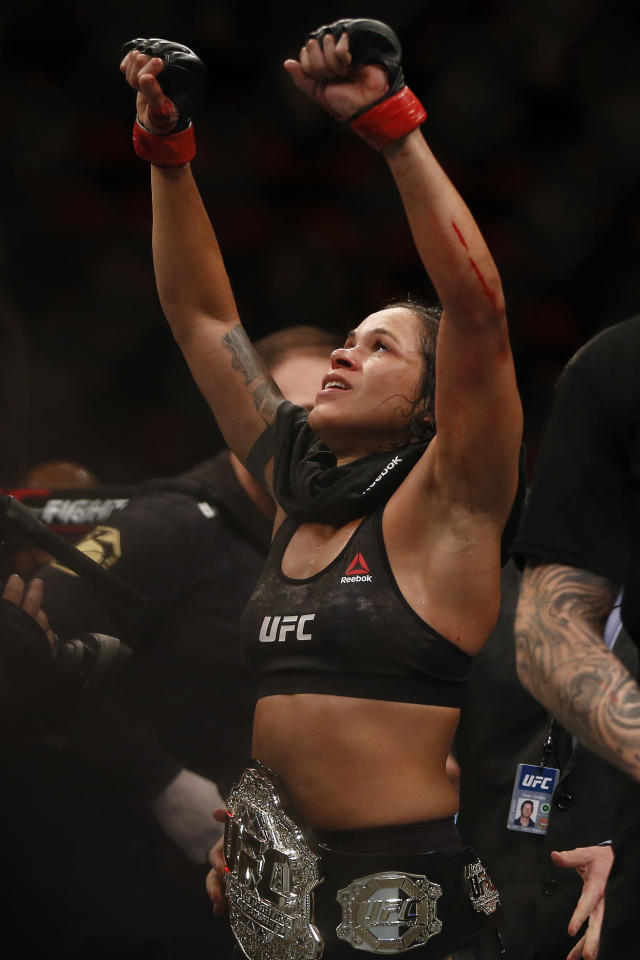 Wearing the champion's belt, Amanda Nunes, from Brazil, celebrates after defeating Raquel Pennington, from the United States, during their UFC women's bantamweight mixed martial arts bout in Rio de Janeiro, Brazil, early Sunday, May 13, 2018. (AP Photo/Leo Correa)