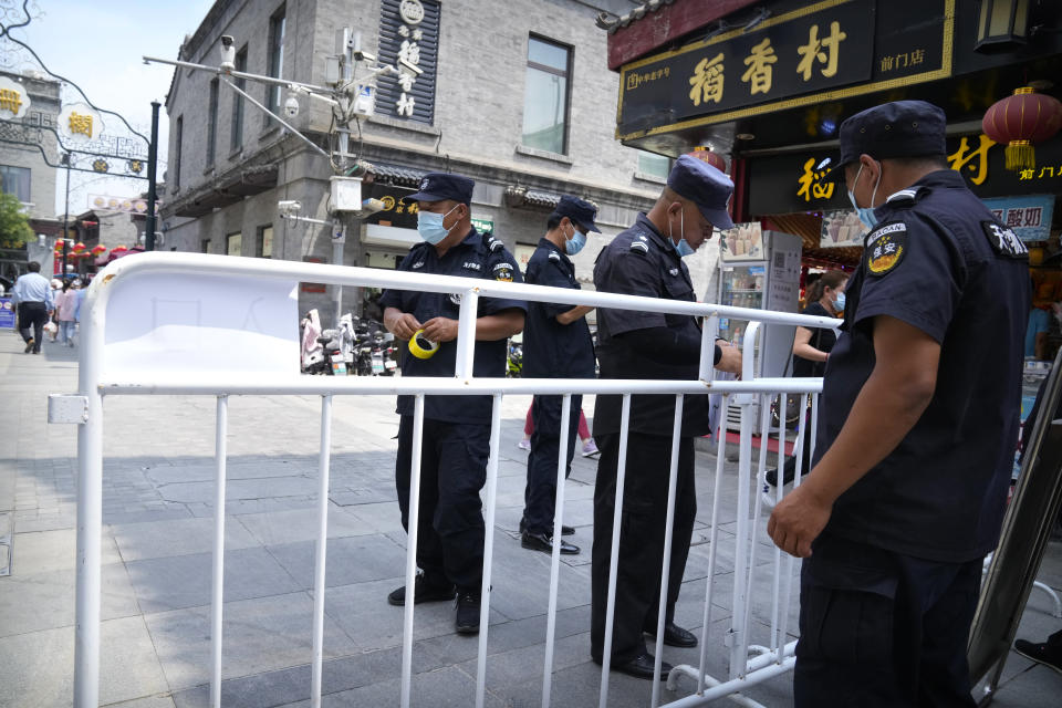 Security guards put up barriers for access control at a tourist shopping street in Beijing, Tuesday, Aug. 3, 2021. Chinese authorities announced Tuesday mass coronavirus testing in Wuhan as an unusually wide series of COVID-19 outbreaks reached the city where the disease was first detected in late 2019. The current outbreaks, while still in the hundreds of cases in total, have spread much more widely than previous ones, reaching multiple provinces and cities including the capital, Beijing. (AP Photo/Mark Schiefelbein)