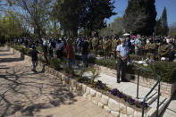 Israelis soldiers and families stand during a ceremony marking the annual Memorial Day for fallen soldiers, at the Kiryat Shaul Military Cemetery in Tel Aviv, Israel, Wednesday, April 14, 2021. Memorial Day is the most solemn day on Israel's national calendar. (AP Photo/Sebastian Scheiner)
