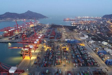 FILE PHOTO: Containers and cargo vessels are seen at sunset at a port in Lianyungang