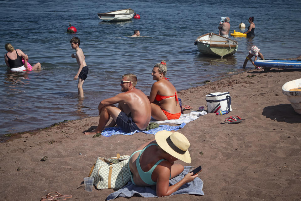 People sunbathe and others swim in the Teign estuary in Shaldon, Devon, England, Wednesday July 21, 2021. Visiting the fishing village of Shaldon a small cluster of mainly Georgian houses and shops at the mouth of the River Teign, is like stepping back into a bygone era. It features simple pleasures that hark back to analog, unplugged summer days: a book and a picnic blanket, a bucket and spade, fish and chips. These are the traditional trappings of the great British seaside holiday that is making a comeback amid foreign travel concerns during the COVID-19 pandemic. (AP Photo/Tony Hicks)