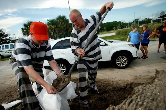 <p>Inmate trustees from the Brevard County Jail work to fill and load sandbags for residents as people in the area prepare ahead of Hurricane Irma on Sept. 7, 2017 in Meritt Island, Fla. (Photo: Brian Blanco/Getty Images) </p>