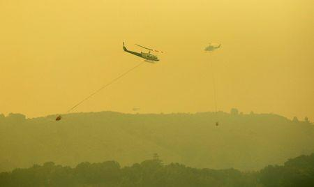 Helicopters pass each other while dropping water on the Soberanes Fire off of Rancho San Carlos Road near Carmel Valley, California, U.S. July 29, 2016. REUTERS/Michael Fiala