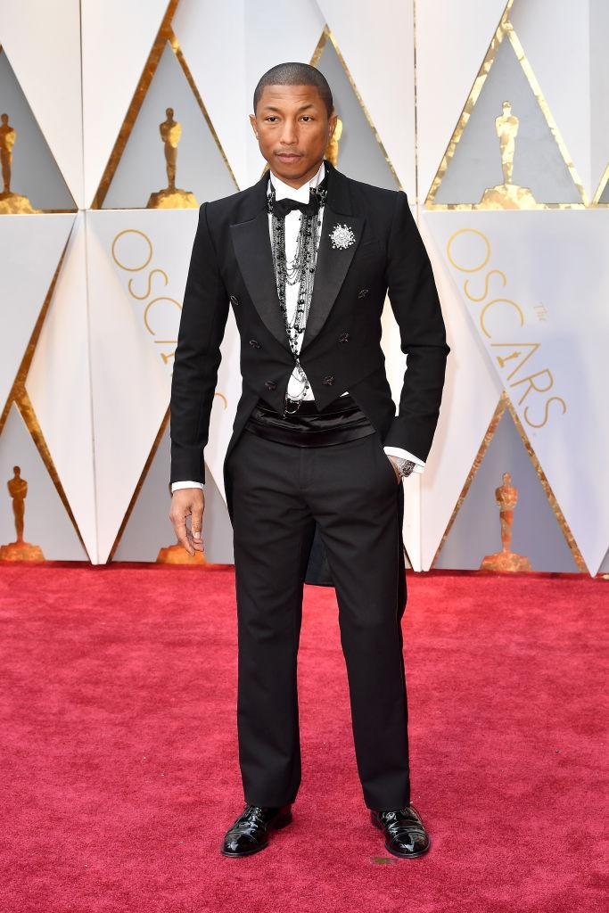 <p>Pharrell Williams, wearing head-to-toe Chanel, accessorized his suit with layers of unique necklaces. <em>(Photo: Getty Images)</em> </p>