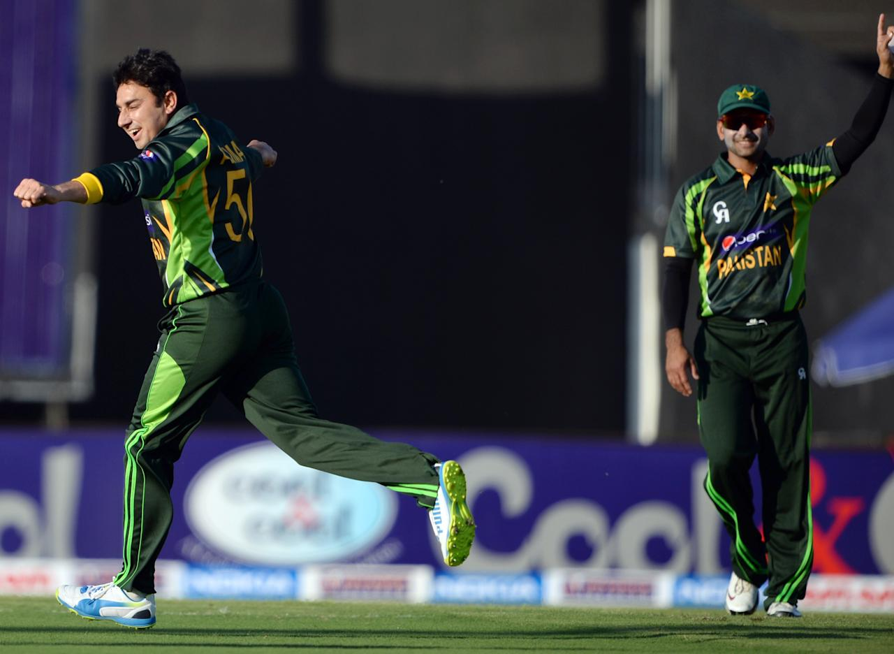 Pakistan's bowler Saeed Ajmal (L) celebrates after taking a wicket of South African Graeme Smith (unseen) during the first one-day in Sharjah Cricket Stadium in Sharjah on October 30, 2013. South African captain AB de Villiers won the toss and decided to bat in the first of five one-day internationals against Pakistan in Sharjah . AFP PHOTO/ Asif HASSAN        (Photo credit should read ASIF HASSAN/AFP/Getty Images)