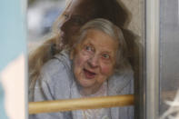 Laura Coriddi talks through a window with her mother Emma Sahl at Northgate Healthcare facility Saturday, March. 6, 2021, in North Tonawanda N.Y. High rates of COVID-19 throughout New York have left the majority of its nursing homes closed for most indoor visits despite relaxed guidance meant to help open them up for visitors. New York updated its visitation rules Thursday, March 25 in a way that will now allow visits to resume under certain conditions, even if a resident has recently tested positive. (AP Photo/Jeffrey T. Barnes)