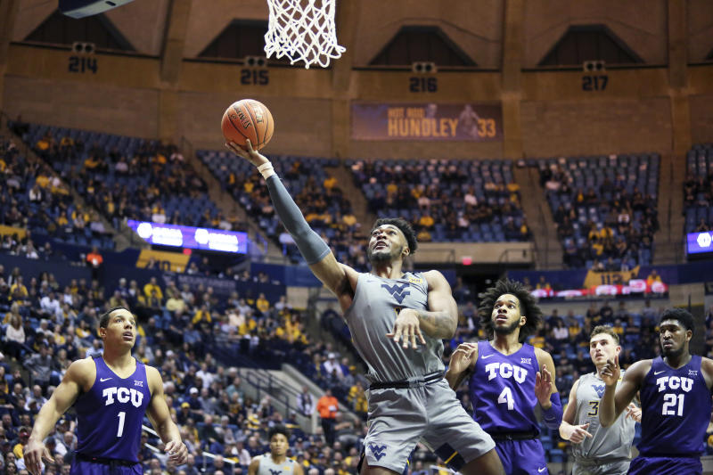 West Virginia forward Derek Culver (1) shoots as TCU guards Desmond Bane (1) and PJ Fuller (4) and TCU center Kevin Samuel (21) defend during the second half of an NCAA college basketball game Tuesday, Jan. 14, 2020, in Morgantown, W.Va. (AP Photo/Kathleen Batten)