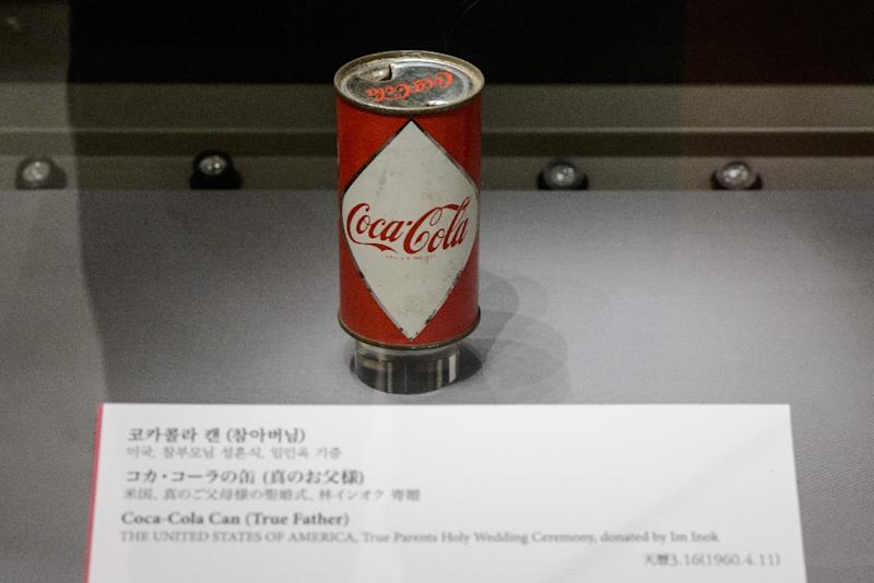Sun Myung Moon sipped from the Coca-Cola can, then handed it to a follower, Kim Hwee-Ok, to finish off (AFP Photo/Ed Jones)