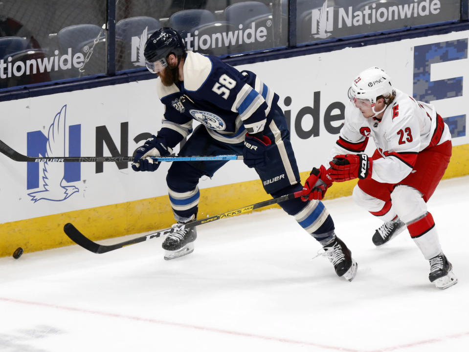 Columbus Blue Jackets defenseman David Savard, left, and Carolina Hurricanes forward Brock McGinn chase the puck during the second period of an NHL hockey game in Columbus, Ohio, Sunday, Feb. 7, 2021. (AP Photo/Paul Vernon)