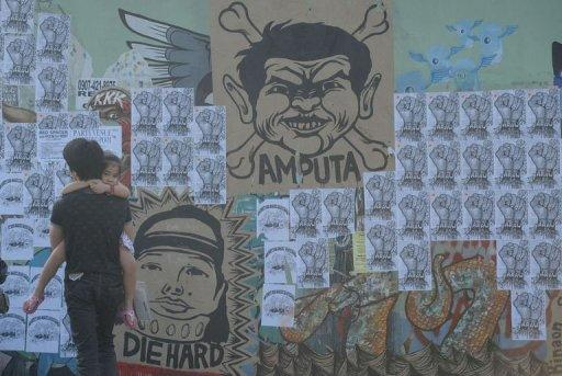 People walk past a wall with a caricature of former Philippine president Gloria Arroyo and Maguindanao massacre suspect Andal Ampatuan at an overpass in Quezon City, east of Manila on November 28, 2011