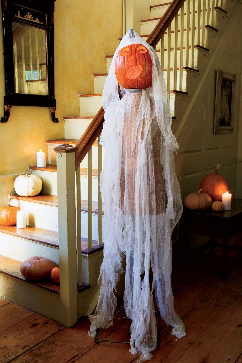 """<p>Give """"dressed to kill"""" a whole new meaning with a pumpkin-headed specter. Carve a grimacing jack-o'-lantern, then carefully attach it to the top of an old dressmaker's dummy. Drape the mannequin with tattered-looking cheesecloth and position it in the foyer to greet party guests. </p>"""