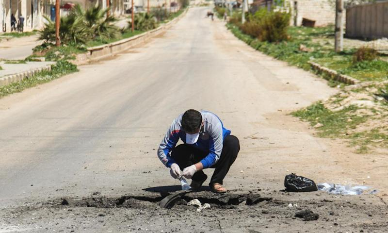 A Syrian man collects samples from the site of the suspected toxic gas attack in Khan Sheikhun.