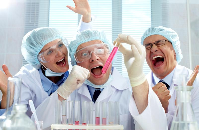 Three scientists celebrate as they look at a test tube filled with a pink substance.
