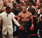 <p>Mike Tyson, center, reacts to the crowd as he leaves the ring following his bout with WBA heavyweight champion Evander Holyfield, Saturday night, June 28, 1997, at the MGM Grand Garden in Las Vegas. Tyson was disqualified after biting Holyfield's ear twice in the third round. (AP Photo/Lennox McLendon) </p>