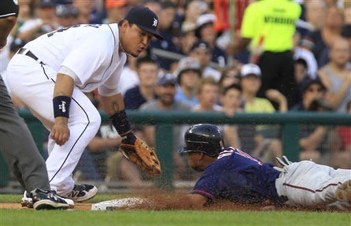 Minnesota Twins' Ben Revere safely slides under the tag of Detroit Tigers third baseman Miguel Cabrera during the fifth inning of a baseball game in Detroit, Monday, July 2, 2012. (AP Photo/Carlos Osorio)