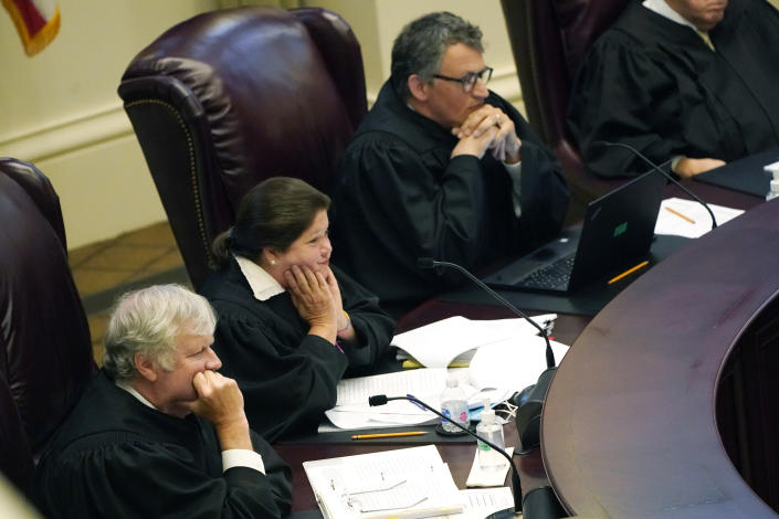 Mississippi Supreme Court Associate Justices T. Kenneth Griffis, left, Dawn Beam, center and Josiah Dennis Coleman, listen to attorneys presenting arguments over a lawsuit that challenges the state's initiative process and seeks to overturn a medical marijuana initiative that voters approved in November 2020, Wednesday, April 14, 2021, in Jackson, Miss. (AP Photo/Rogelio V. Solis)