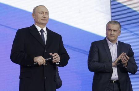 Russian President Vladimir Putin and Crimean Prime Minister Sergei Aksyonov attend a festive concert marking the first anniversary of the Crimean treaty signing in central Moscow