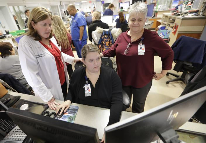 In this Thursday, Dec. 19, 2019 photo, Kathleen Sheehan, left, director of Emergency and Trauma Services, speaks with Sarah Horn, center, and Lead Case Manager Jeanne Icolari in the Emergency room at St. Luke's Cornwall Hospital in Newburgh, N.Y. The hospital adopted the Hudson Valley Interlink Analytic System earlier this year, which tracks drug overdoses in New York. The system is among a number of surveillance systems being adopted around the country by police, government agencies and community groups. (AP Photo/Frank Franklin II)