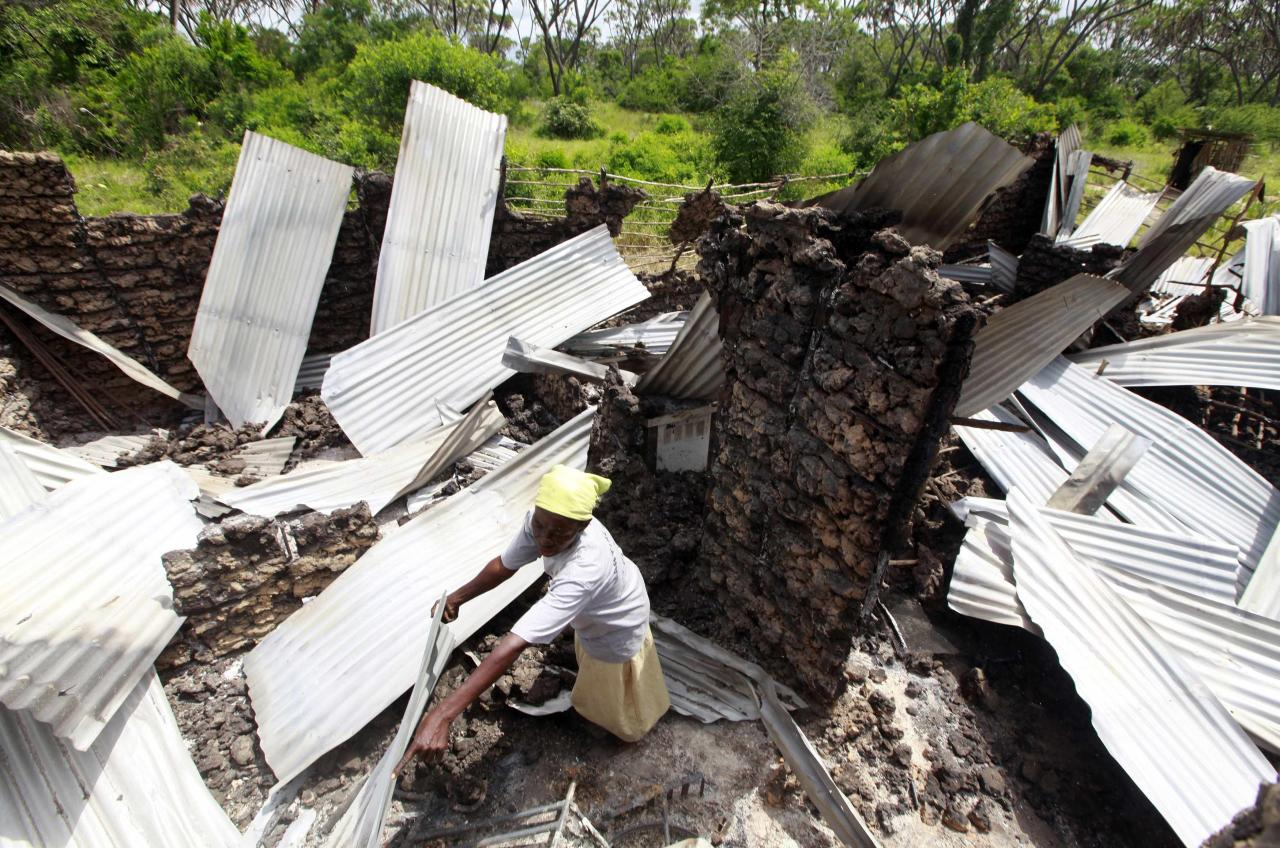 A resident rummages through the ruins of her building burnt down after gunmen attacked Hindi village, near Kenya's coastal town of Lamu, July 6, 2014. Gunmen killed at least 29 people in raids on two separate areas on the Kenyan coast, the interior ministry said on Sunday. The Somali Islamist militant group al Shabaab said it had staged an attack on Saturday evening in the coastal area. Nine people lost their lives at the Hindi trading centre in Lamu county, near the scene of attacks in which 65 people were killed last month, Mwenda Njoka, the ministry's spokesman told Reuters. REUTERS/Joseph Okanga (KENYA - Tags: CIVIL UNREST CRIME LAW)