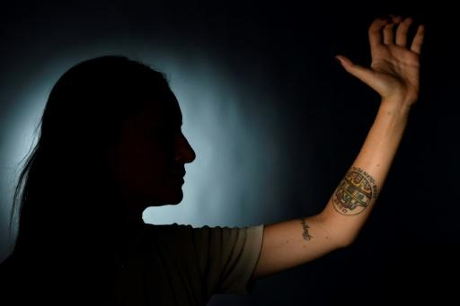 One of the victims who was wounded at Paris' Bataclan concert hall during the November 2015 attacks shows her tattoo bearing the date 13-11-2015